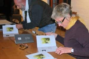 Jenny Parsons and Solly Smook signing catalogues of the Solo Studios 2017 Linocut Project