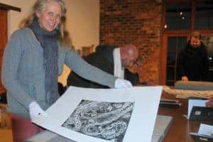 Greta McMahon looking at her limited edition linocut print.