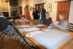 Artists signing limited edition prints of the Solo Studios 2017 Linocut Project.